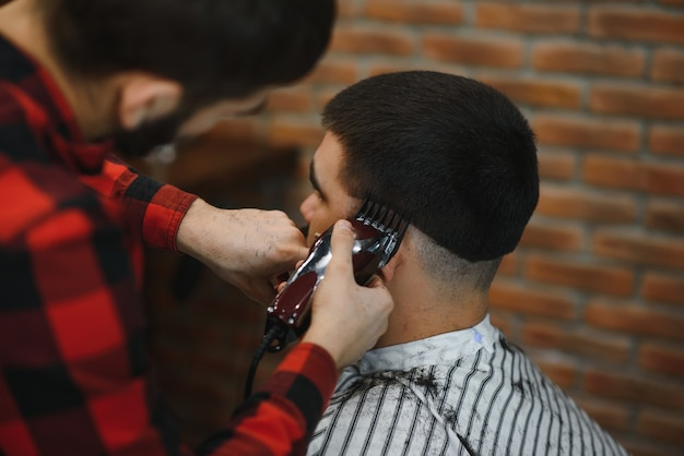 Barber shop. man in barber's chair, hairdresser barbershop styling his hair