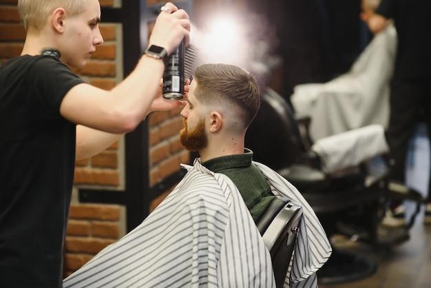Парикмахерская. мужчина в кресле парикмахера, парикмахер укладывает волосы