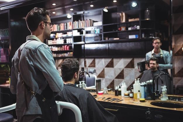 Парикмахер показывает мужчине его стрижку в зеркале