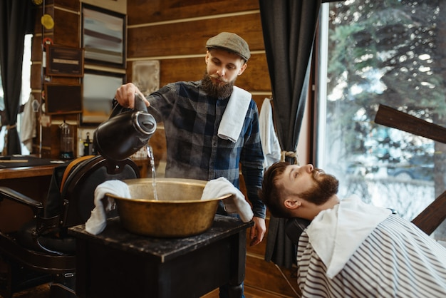 Barber soaks the towel, beard cutting. professional barbershop is a trendy occupation. male hairdresser and client in hair salon
