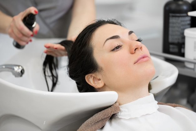 Barber splashes on the client hair spray for easy combing