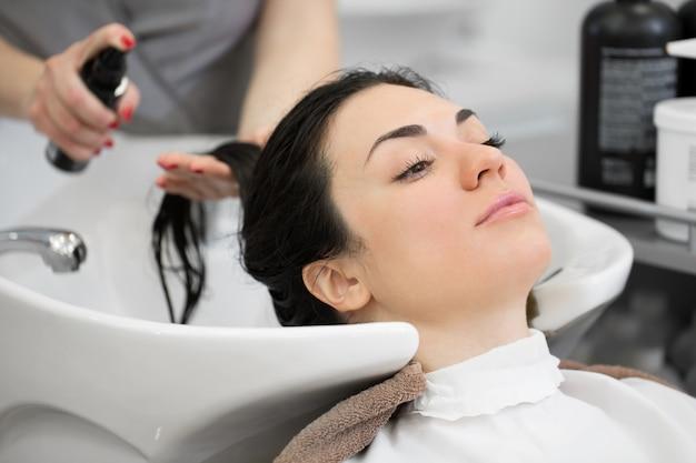Парикмахерская брызгает на клиента лаком для волос для легкого расчесывания