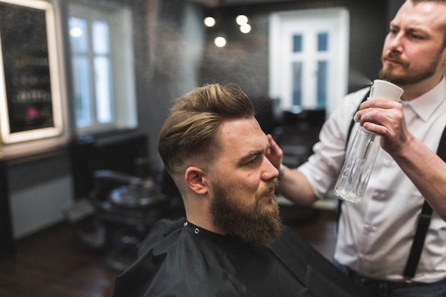 Barber spraying hair of man