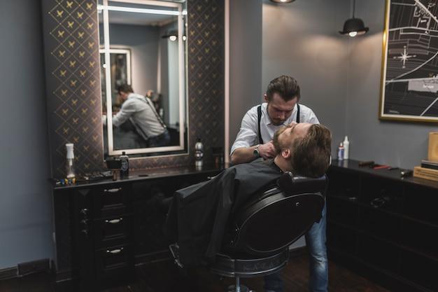 Barbiere styling barba del cliente