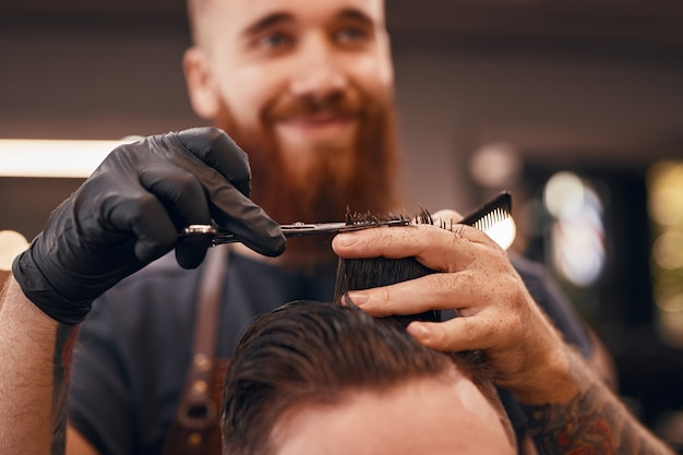 Barber styling hair of a customer