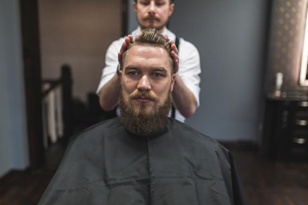 Укладка парикмахера волосами клиента муссом