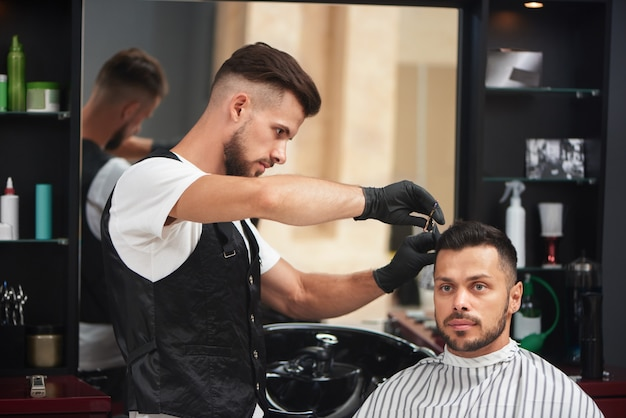 Barber styling haircut of man using comb and scissors.