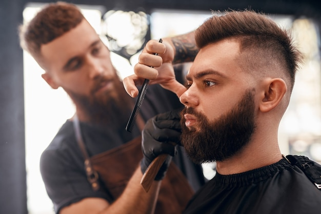 Barber trimming beard of client in barbershop