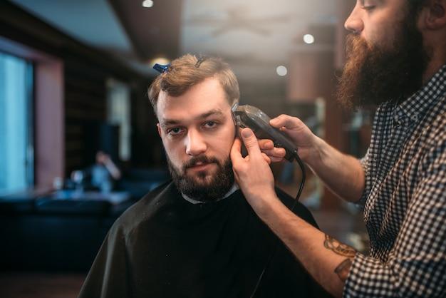 Парикмахер стрижет волосы клиента машинкой для стрижки.