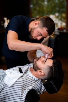 Barber trimming a man's beard