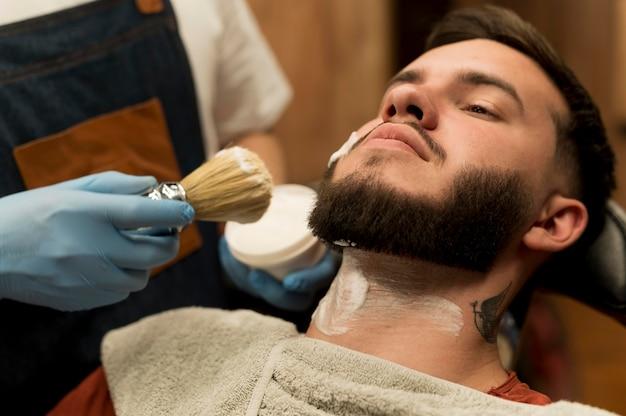 Barber using shaving cream to contour male customer's beard