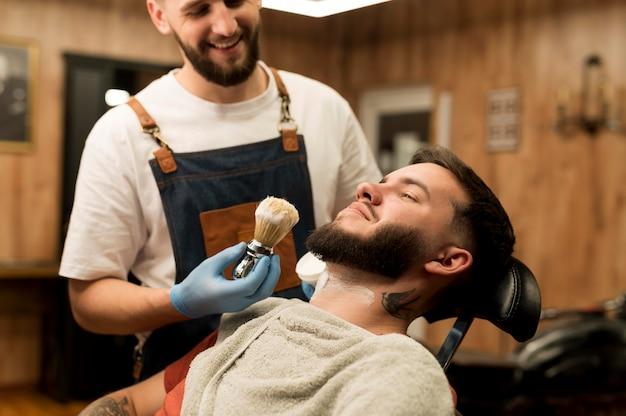 シェービングクリームを使って男性客のひげを整える理容師