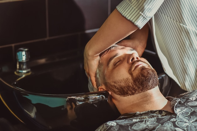 The barber washes the hair of a bearded man before a haircut
