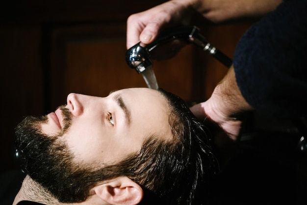Barber washes hair of bearded man
