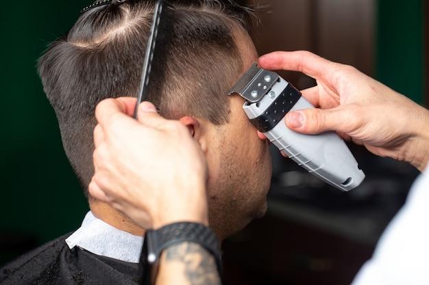 Barbiere mentre lavora con il taglio di capelli