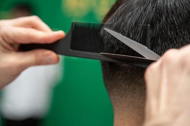Barbiere mentre si lavora con taglio di capelli