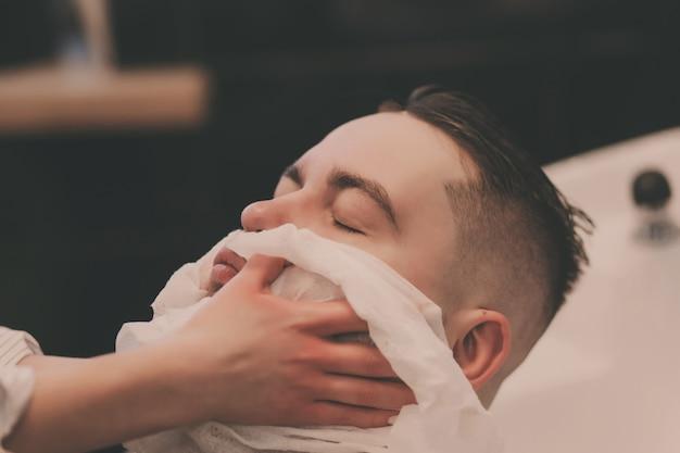 Парикмахер вытирает бороду мужчине после мытья в парикмахерской