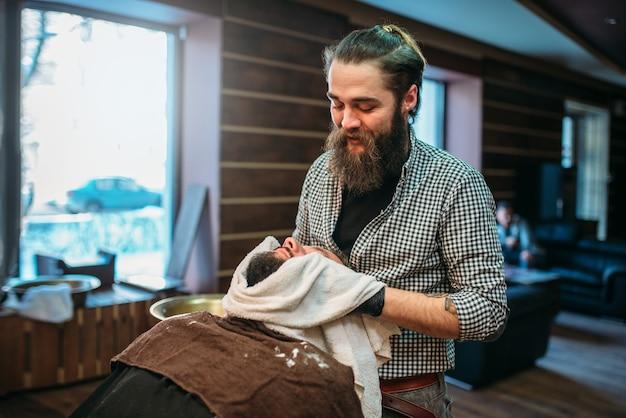 クライアントのひげをタオルで拭く床屋