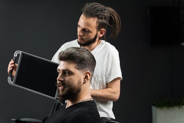 理髪店でひげを生やした男性のために低フェードマシンの髪とひげをカットした結果を示すドレッドヘアの床屋。スムーズな移行のヘアスタイル。