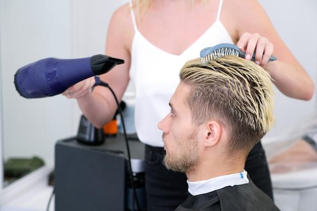 クライアントのヘアドライヤー乾燥とスタイリングヘアを備えた理髪店。ヘアドライヤー付きの理髪店は、ひげを生やした男性、理髪店の背景の髪型に取り組んでいます。スタイリングコンセプト