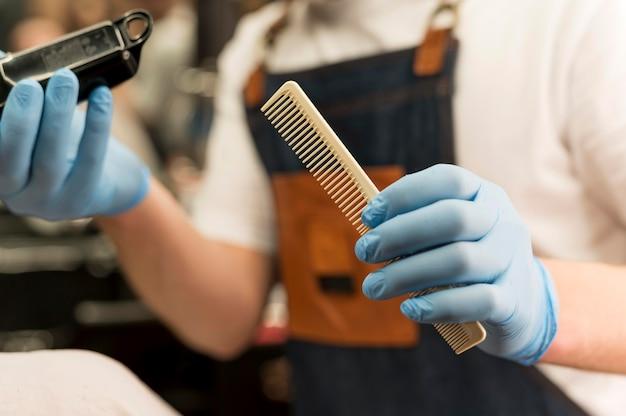 Barbiere con guanti in lattice che tengono trimmer e pettine
