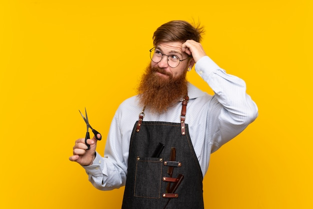 Barber with long beard in an apron over isolated yellow background having doubts and with confuse face expression