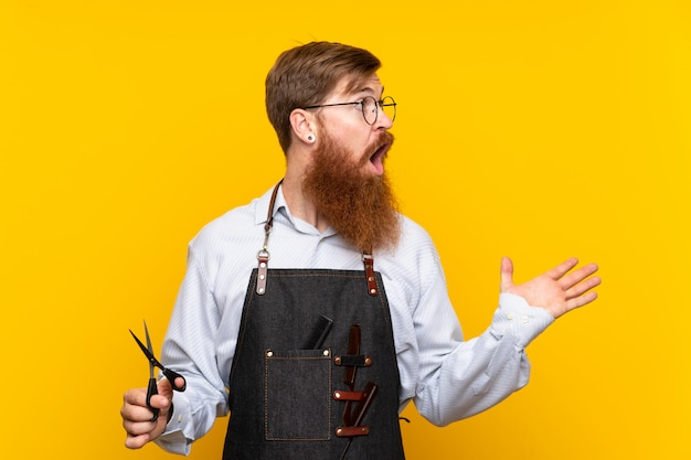 Barber with long beard in an apron over isolated yellow background with surprise facial expression