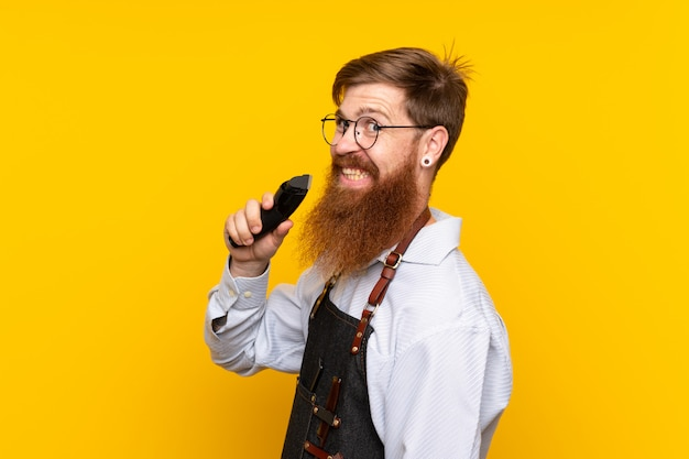 Barber with long beard in an apron over isolated yellow wall