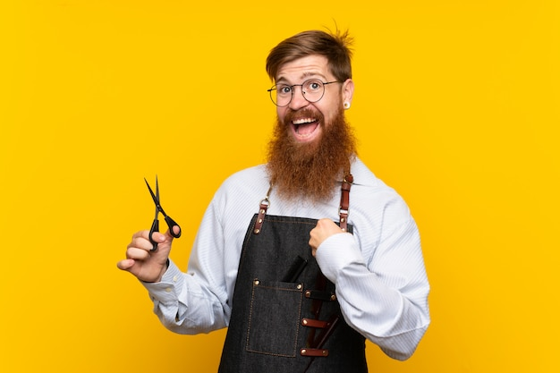 Barber with long beard in an apron yellow with surprised facial expression