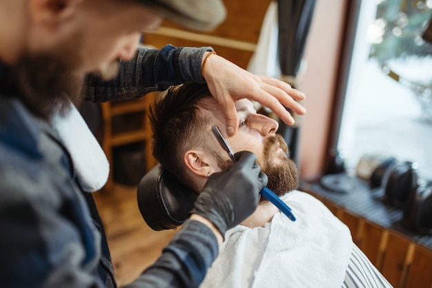 Barber with razor, old school beard cutting. professional barbershop is a trendy occupation. male hairdresser and client in hair salon