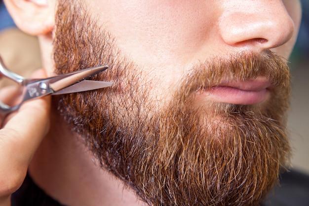 あごひげを生やした男を剃るはさみで床屋。男性の美しさの屋内ショット