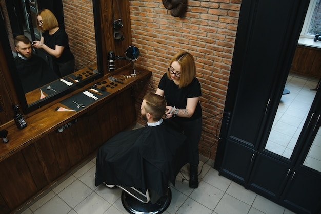 理髪店で男の髪を切る理髪店の女性。美容師として働く女性。中小企業の概念。