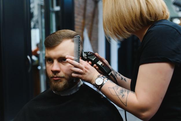 理髪店で男の髪を切る理髪店の女性。