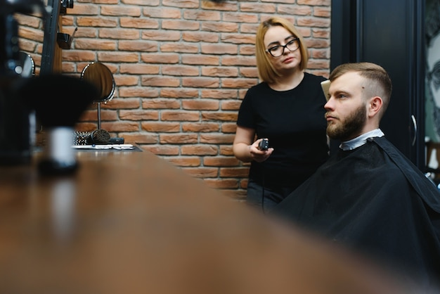 Barber woman cutting man hair at the barbershop. woman working as a hairdresser. small business concept.