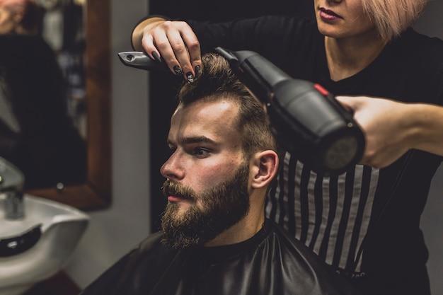 Женщина-парикмахерская сушка волос клиента