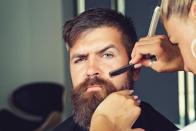 이발소나 미용실에서 고객의 수염을 면도하는 이발사. 살롱에서 수염을 면도하는 남성 고객의 초상화. 직장에서 이발사입니다. 이발소에서 남자입니다. 이발소에서 수염을 기른 잘생긴 남자.