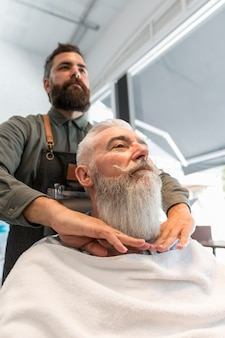 Barber working with aged client in salon