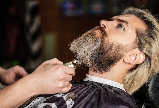 이발사는 수염깎이로 일합니다. 힙스터 클라이언트가 머리를 자르고 있습니다. 손 미용사