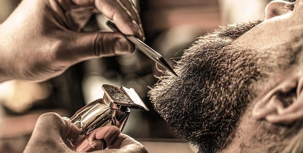 이발사는 수염깎이로 일합니다. 힙스터 클라이언트가 머리를 자르고 있습니다. 수염 깎기, 근접 촬영으로 미용사의 손. 이발소에서 수염 난된 남자입니다. 이발소에서 미용사를 방문하는 남자.