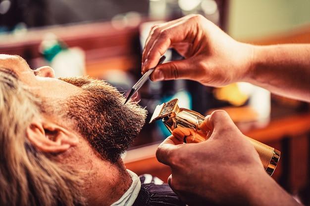 이발사는 수염깎이로 일합니다. 힙스터 클라이언트가 머리를 자르고 있습니다. 수염 깎기, 근접 촬영으로 미용사의 손.