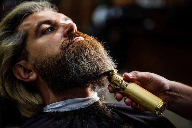 Barber works with a beard clipper. hipster client getting haircut. hands of a hairdresser with a beard clipper, closeup.