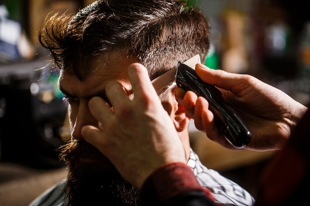 Barber works with hair clipper.