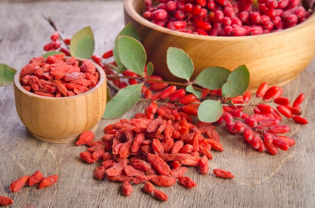 Barberry and dry goji berries in bowls on wooden