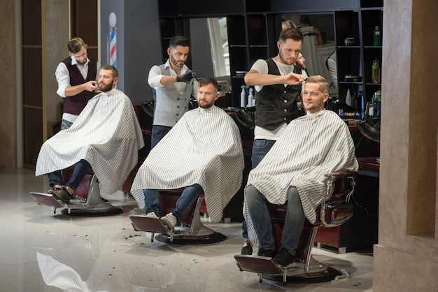Barbers grooming and styling haircuts of clients in barbershop.