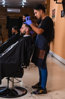 Barbers working in their men's salon - two bearded barbers giving haircuts to male customers in the barber shop .