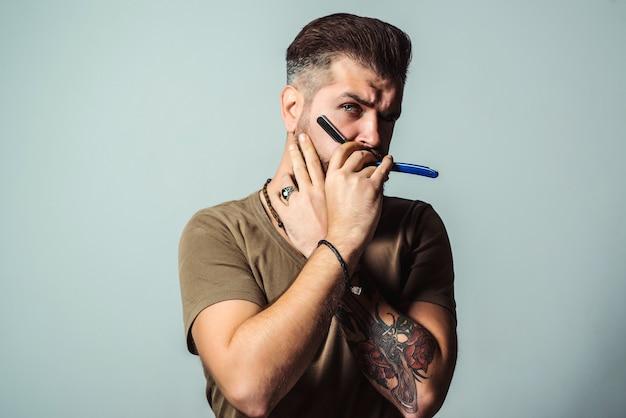 Barbershop. barber holds straight razor for shaving his beard.
