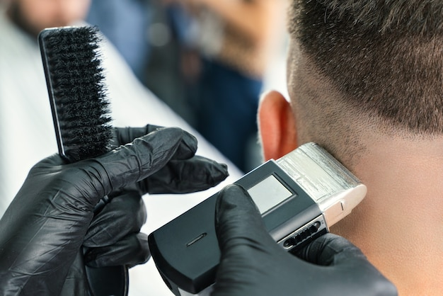 Barbershop client. man getting his beard trimmed with electric razor
