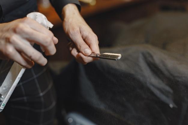 理髪店。床屋のクローズアップは彼のひげを剃るためのかみそりを保持します