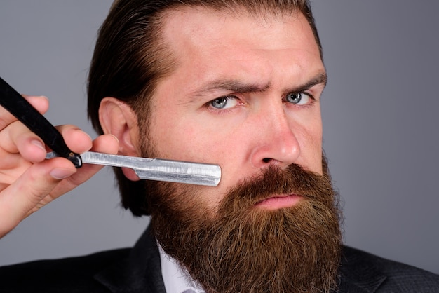 Barbershop close up portrait of bearded man with razor handsome bearded man with hairdresser or
