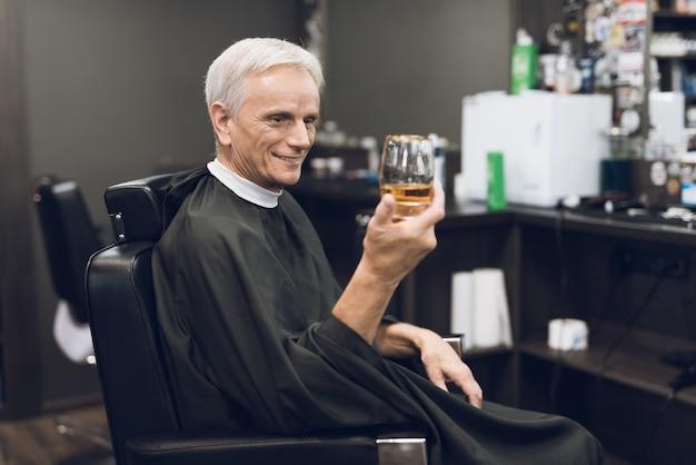 Barbershop elderly client drinks alcohol